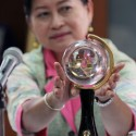 Piala untuk pemenang Anugerah jurnalistik Adinegoro, di tangan ketua panitia penjurian, Maria Andriana.