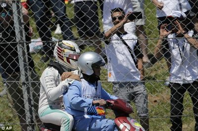 Lewis Hamilton dibonceng ke pit setelah tabrakan pada laga F1 Barcelona, Minggu. (dailymail.co.uk)