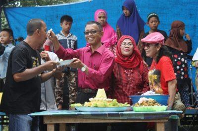 Camat Teluk mengkudu,Misran, memberikan potongan tumpeng kepada ketua SANTAI Sujarwo.  (AL)