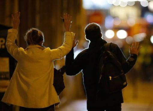Dua warga berjalan ke arah polisi dengan tangan terangkat, menunjukkan tangan, setelah terjadi peristiwa penembakan. (Foto: Reuters/BBC News)