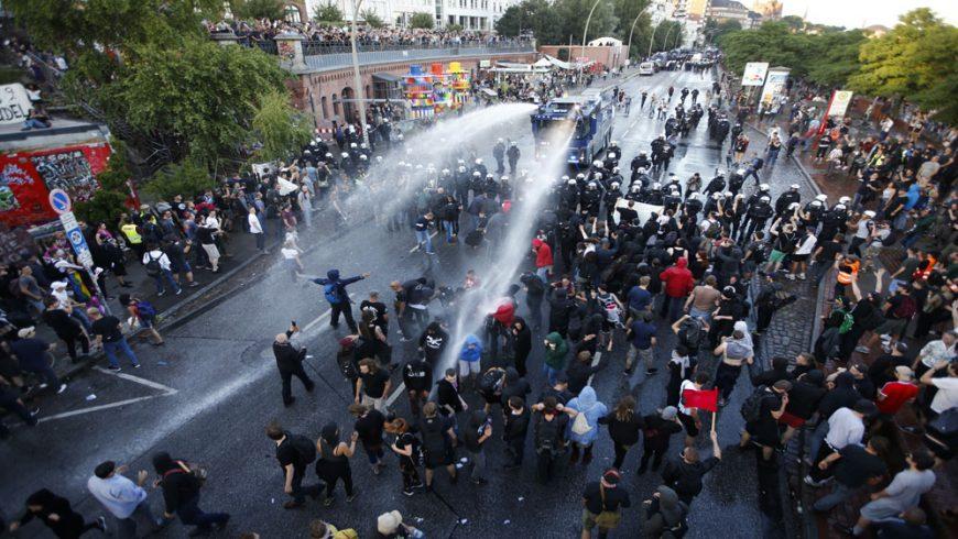 Polisi anti huru hara Jerman menggunakan meriam air, tongkat, dan semprotan merica dalam menghadapi demonstran menentang G20 KTT di Hamburg, Jerman, Kamis (6/7). [Foto: Reuters/Al Jazeera)