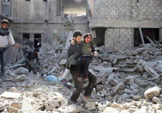 Seorang pria membawa anak laki-laki yang terluka saat ia melewati bangunan-bangunan yang hancur akibat pengeboman di Ghouta Timur, Suriah, Rabu (21/2). (Foto: Reuters/Al Jazeera)