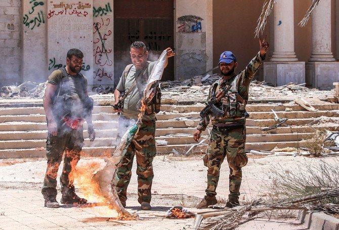 Tentara pemerintah Suriah membakar sebuah bendera oposisi di penyeberangan perbatasan Nassib dengan Yordania, di provinsi selatan Daraa, pada 7 Juli 2018 lalu. (Foto: AFP/Arab News)