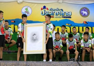 Anak-anak anggota tim sepakbola yang diselematkan itu memegang foto penyelam Saman Kunan yang meninggal dalam operasi penyelamatan. (Foto: Reuters/Al Jazeera)