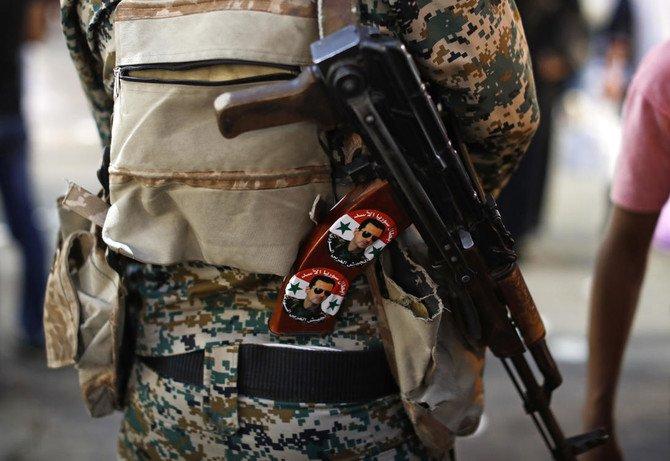 """Seorang tentara Suriah memegang senapan AK-47 yang ditempeli stiker Presiden Bashar Assad bertuliskan bahasa Arab yang berbunyi, """"Pahlawan Suriah Assad,"""" di pos pemeriksaan di pasar Hamadiyah, di Kota Tua dari Damaskus, Suriah. Foto ini diabadikan 19 Juli 2018. (Foto: Dokumentasi AP/Arab News)"""