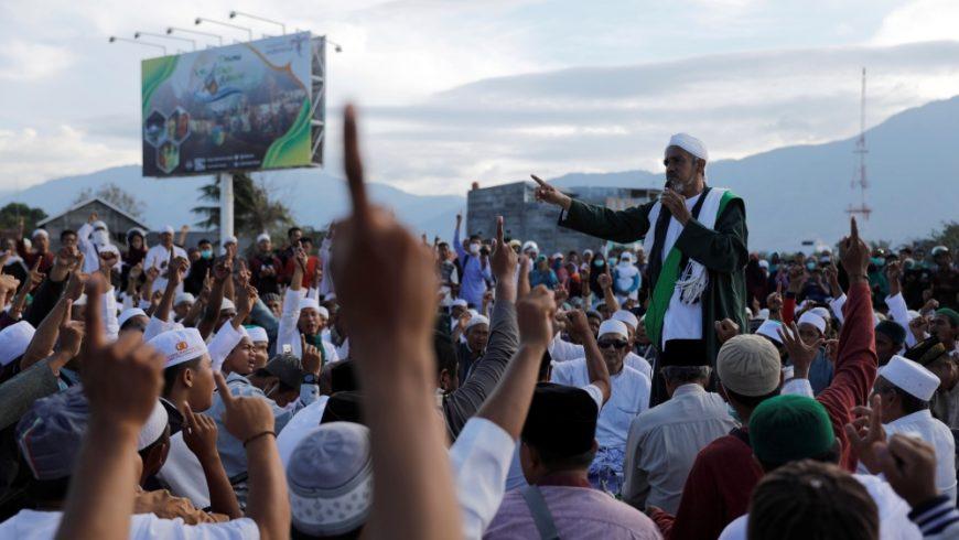 Seorang ustadz menyampaikan kajdian dan memimpin doa massal untuk Palu di pantai Talise. (Foto: Reuters/Al Jazeera)