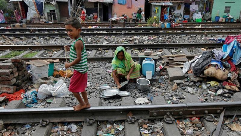 Seorang anak laki-laki meeniti rel melewati seorang wanita yang membersihkan peralatan dapurnya di antara rel kereta api di daerah kumuh Kalkuta, India. (Foto:Reuters/Al Jazeera)