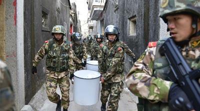 Polisi paramiliter membawa shabu kristal yang disita saat penumpasan di Tiongkok selatan (Foto: Reuters/Al Jazeera)