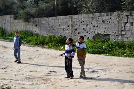 Dinding perbatasan penuh lubang akibat peluru dan pecahan peluru menutupi dinding. Foto diabadikan ketika anak-anak bermain layang-layang di Kota Gaza, 12 Februari 2019. (Foto: Reuters/Arab News)