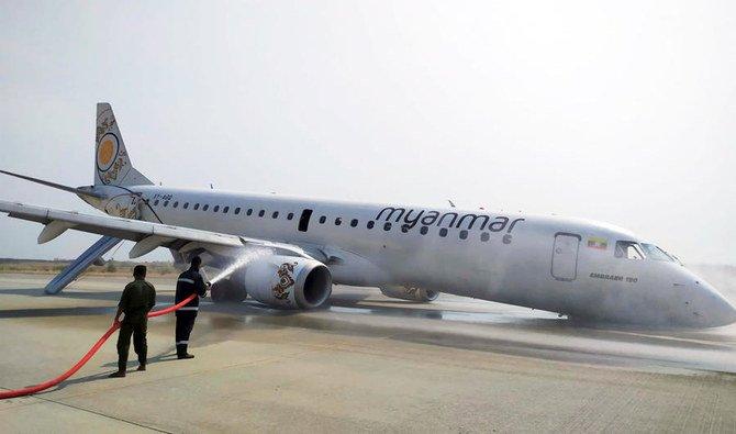 Petugas pemadam kebakaran melakukan penyemprotan pemadam untuk mengamankan pesawat Myanmar National Airline (MNA), yang mengalami kecelakaan di bandara Internasional Mandalay, Myanmar, Minggu (12/5). (Foto: AP/Arab News)