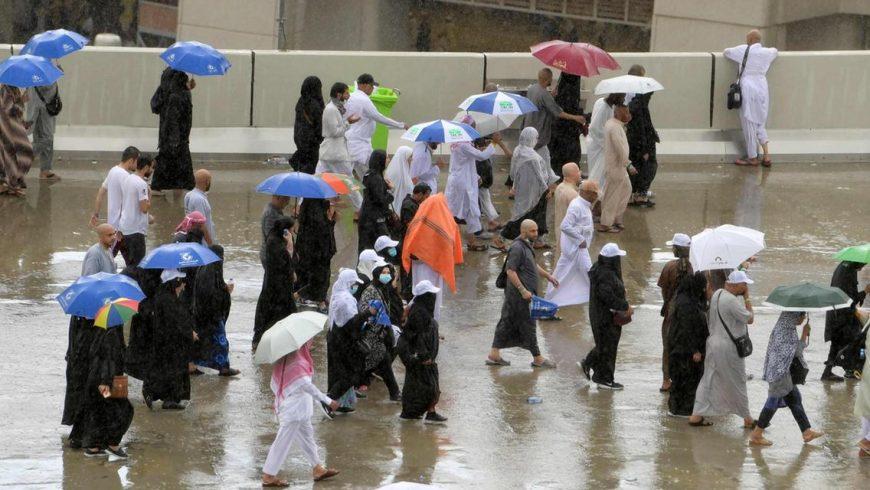 Hujan menguyrur umat Muslim saat menjalani ritual melempar jumrah, Senin (12/8) di Mina. (Foto: AFP/The National)
