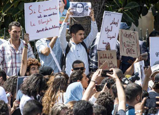 Para pengunjuk rasa mengacungkan berbagai pamflet termasuk potret Hajar Raissouni, seorang wartawa Maroko dari surat kabar harian Akhbar El-Youm, di luar gedung pengadilan yang mengadakan persidangan atas tuduhan aborsi di Rabat, 9 September 2019.(Foto: AFP/France24)