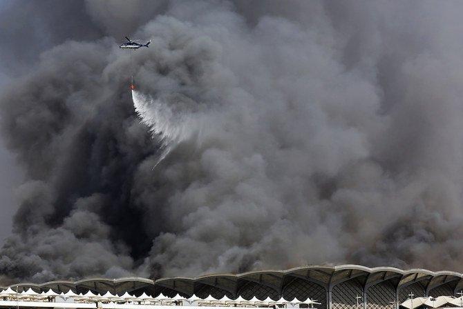 Helikopter pemadam kebakaran menyemprotkan air ke kobaran api di stasiun Haramain di Jeddah. (Foto: AP/Arab News)