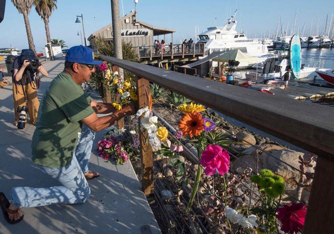 Seorang lelaki meletakkan bunga di dekat tambatan Truth Aquatics, dekat terbakarnya kapal. (Foto: AFP/Arab News)