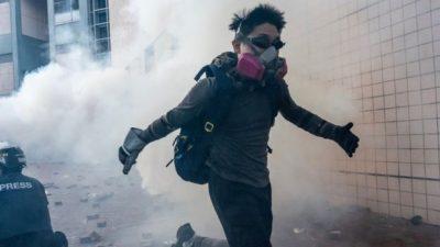 Seorang pemrotes anti-pemerintah Hong Kong dengan mengunakan topeng melintas di sasaran tembak gas air mata aparat.(Foto:Getty Images/BBC)