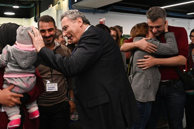 Pengungsi Suriah Ibrahim Bitar, 42 (berbaju merah, kanan) dan saudara perempuannya Iman Bitar (kedua dari kanan) berangkulan saat Presiden Komunitas Sant'Egidio, Marco Impagliazzo (tengah) menyambut para pengungsi Suriah tiba di bandara internasional Fiumicino Roma, 27 November , 2019. (Foto:AFP/Arab News)