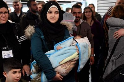 Seorang wanita Suriah menggendong bayi ketika sejumlah pengungsi Suriah tiba di bandara internasional Fiumicino Roma Rabu 27 November 2019. (Foto: AFP/Arab News)