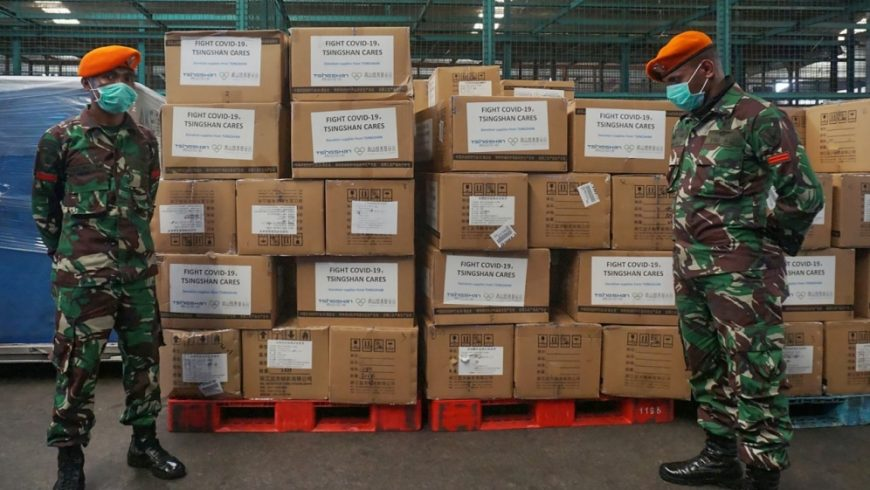 Tentara Indonesia berjaga-jaga di sebelah kotak-kotak peralatan medis dan bantuan yang tiba dari China pada Jumat (27/3) pagi.( Foto: AFP/Al Jazeera)