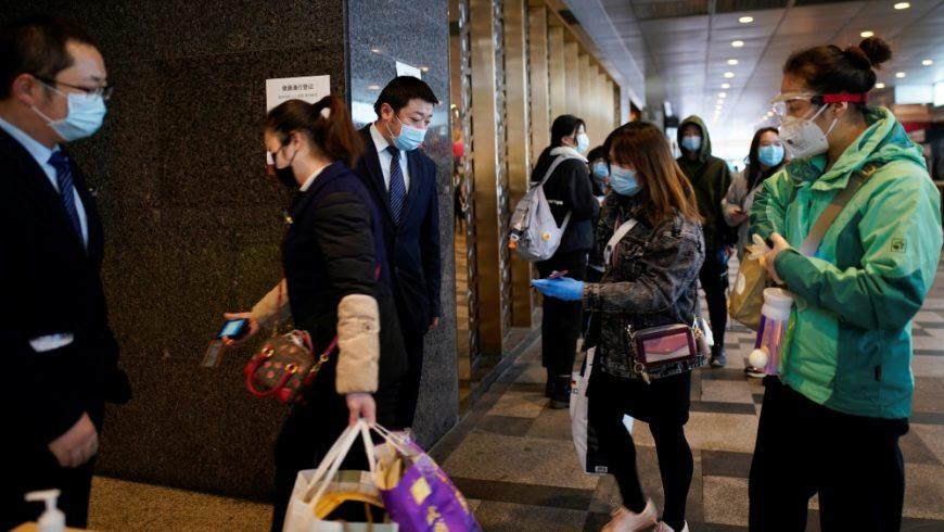 Demi pengamanan, staf manajemen memeriksa kode QR pada ponsel karyawan dan pengunjung yang akan memasuki pusat perbelanjaan di pintu masuknya di Wuhan, provinsi Hubei, pada 30 Maret 2020.(Foto: Reuters/Al Jazeera)
