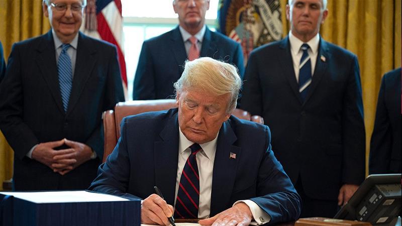 Presiden Amerika Serikat Donald Trump menandatangani Undang-Undang Bantuan Korona, Bantuan, dan Keamanan Ekonomi (CARES), paket penyelamatan $ 2,2 triliun untuk memberikan bantuan ekonomi di tengah wabah koronavirus. (Fotto: AFP/Al Jazeera)