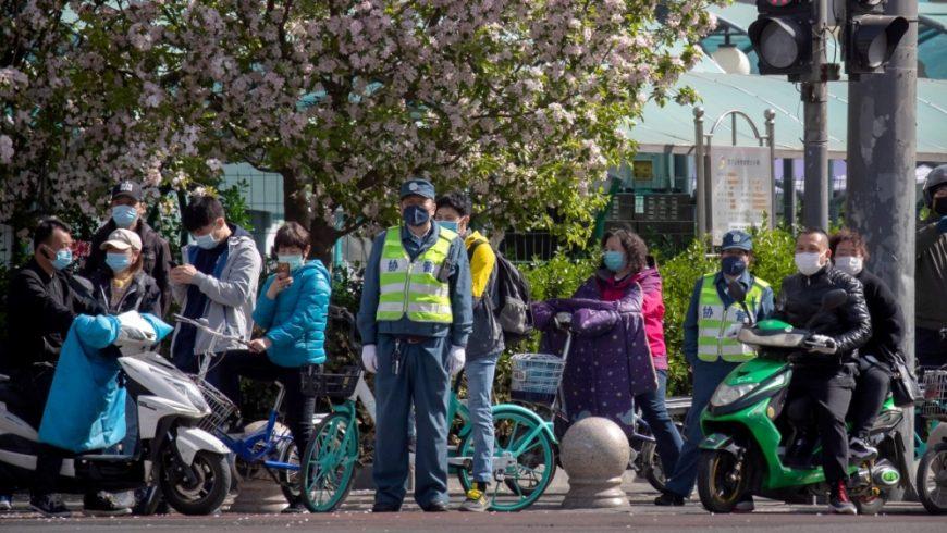 Orang-orang berhenti di persimpangan saat momen berkabung nasional untuk para korban coronavirus di Beijing pada hari Sabtu (4/4). (Foto: AP/Al Jazeera)