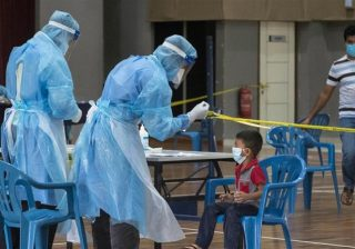 Seorang anak diuji untuk COVID-19 di fasilitas pengujian sementara yang didirikan oleh Kementerian Kesehatan Malaysia di sebuah pusat komunitas di pinggiran Kuala Lumpur. (Foto: Al Jazeera]