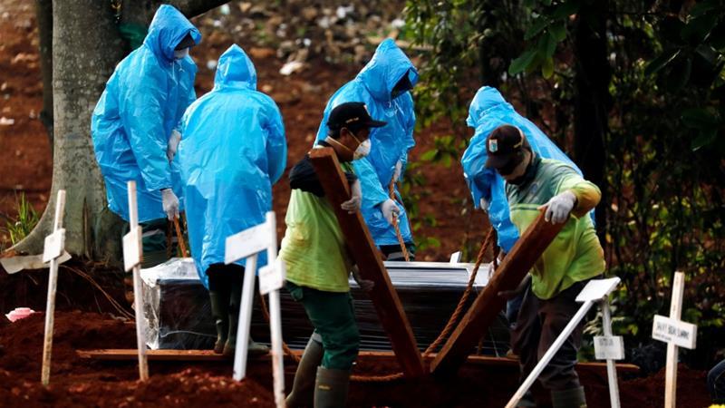Pekerja kota mengenakan jas hujan sebagai alat pelindung saat mengubur korban COVID-19 di pemakaman di Jakarta, Indonesia, baru-baru ini.(Foto: Reuter/Al Jazeera)