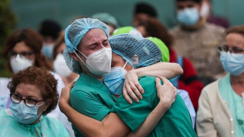 Petugas kesehatan di Spanyol berpelukan bersama kolega pertanda duka atas meninggalnya rekan mereka karena COVID-19. (Foto: Reuter/Al Jazeera)
