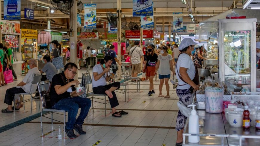 Orang-orang berupaya menjaga jarak sosial duduk dan makan di sebuah pasar di Bangkok, setelah pembatasan dilonggarkan minggu ini.(Foto: AP/Al Jazeera)