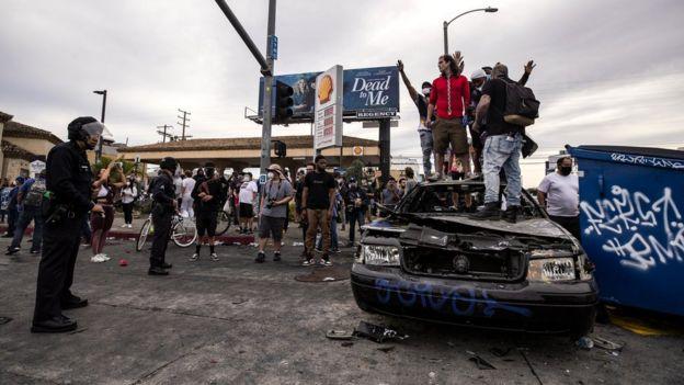 Para pengunjuk rasa berdiri di atas sebuah mobil polisi yang telah terbakar di Los Angeles, California.(Foto: EPA/BBC News)