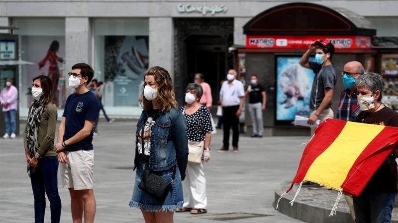 Orang-orang dengan menggunaan masker berdiri 'selama satu menit' setiap hari untuk mengenang para korban virus korona di Madrid. (Foto: Reuters/Al Jazeera)