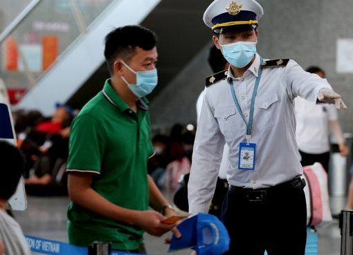 Seorang anggota staf dari Pusat Pengendalian Penyakit Vietnam membantu penumpang di bandara internasional Danang pada 27 Juli 2020. (Foto AFP/Al Jazeera)