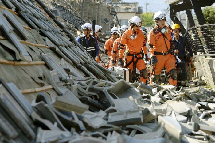Para petugas pertolongan ketika menyusuri puing-puing akibat gempa.