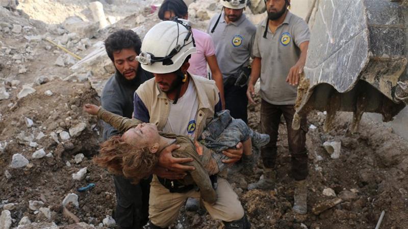 """Kelompok """"Helm Putih"""" tampak menyelamatkan seorang anak dari puing bekas hantaman serangan udara. Pihak penyelamat mengatakan bahwa pihaknya juga berulang kali jadi target dalam perang Suriah. (Foto:AFP/Al Jazeera)"""
