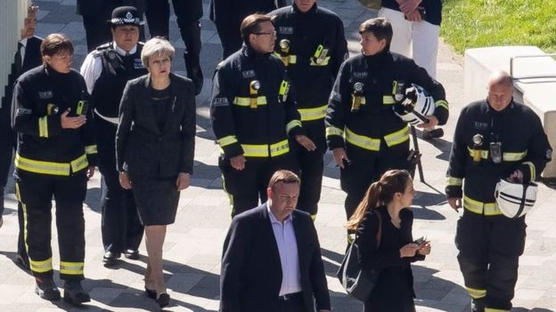 Perdana Menteri Inggris Theresa May berbicara dengan beberapa petugas pemadam saat melakukan peninjauan di lokasi kebakaran. (Foto: Copyright Getty Images/BBC News)