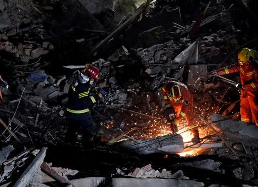 Pemadam kebakaran bekerja di lokasi gedung yang runtuh di Shanghai. (Foto: Reuters/Al Jazeera)