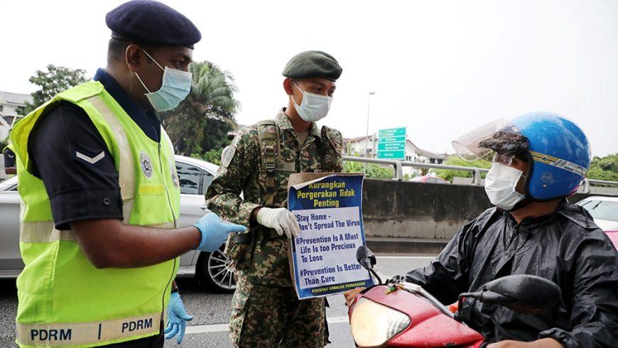 Seorang tentara dan seorang polisi menunjukkan plakat pembertahuan kepada pengendara sepeda motor di sebuah pos yang didirikan untuk menegakkan perintah gerakan kontrol di Kuala Lumpur, Malaysia. (Foto: Reuters/Al Jazeera)