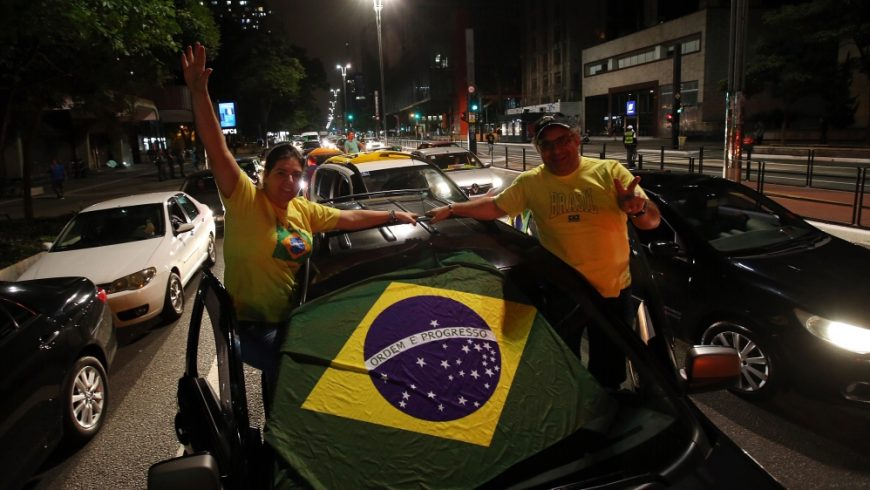 Pendukung Presiden Jair Bolsonaro mengibarkan bendera Brasil ketika mereka mengambil bagian dalam iring-iringan mobil untuk memprotes tindakan karantina dan jarak sosial untuk memerangi wabah virus corona baru pada 18 April 2020, di Sao Paulo. (Foot: Getty Images/Al Jazeera)