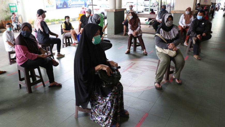 Orang-orang memakai masker dan mempraktikkan jarak sosial untuk mencegah penyebaran coronavirus baru di sebuah supermarket di ibukota Indonesia, Jakarta, Jumat (17/4). (Foto: AP/Al Jazeera)
