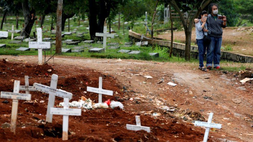 Area makam korban koronavirus (COVID-19) di Jakarta. Kerabat yang memakai masker wajah berdiri di sebelah kuburan korban virus corona di sebuah area pemakaman yang disediakan oleh pemerintah di Jakarta, Indonesia, pada 3 April 2020.(Footo: Reuters/Al Jazeera)