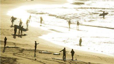 Orang-orang kembali berselancar ketika Pantai Bondi dibuka kembali setelah ditutup untuk mengekang penyebaran coronavirus.(Foto: Reuters/Al Jazeera)