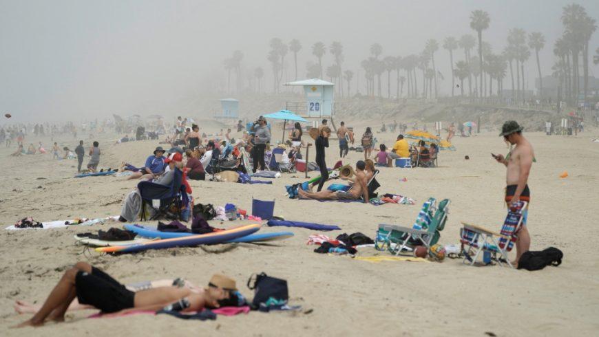 Orang-orang duduk berkelompok di Huntington City Beach di tengah mewabahnya penyakit coronavirus di Huntington Beach, California, AS. Gubernur California Gavin Newsom mendesak orang-orang yang mengunjungi pantai untuk mempraktikkan jarak sosial.(Foto: Reuters/Al Jazeera)