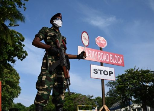 Seorang personil militer Sri Lanka yang mengenakan masker wajah memegang tanda berhenti di sebuah pos pemeriksaan selama penguncian nasional yang diberlakukan pemerintah, sebagai langkah pencegahan terhadap wabah COVID-19 di Kolombo pada 29 April 2020. (Fot: AFP/Al Jazeera)