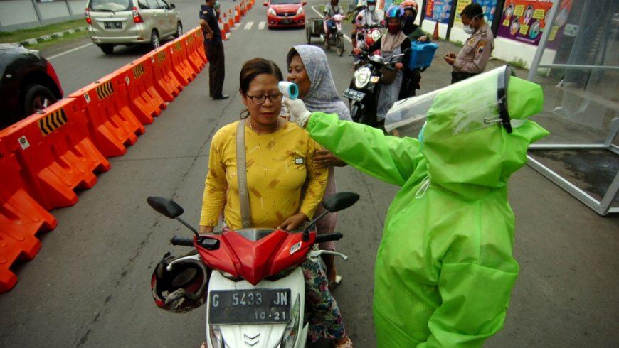 Seorang petugas medis yang mengenakan pakaian pelindung, memeriksa seorang wanita dengan pemindai termal di tengah wabah penyakit corona (COVID-19), di Tegal, Jawa Tengah.(Foto: Reuters/Al Jazeera)