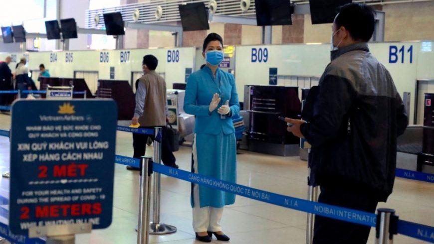 Seorang staf maskapai penerbangan menginstruksikan kepada penumpang bagaimana cara check in di bandara Hanoi, Vietnam, sambil menjaga jarak sosial. (Fot: AP/Al Jazeera)