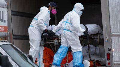 Pekerja memindahkan mayat ke truk berpendingin dari rumah duka yang ada di New York City. Hal itu mendapat kecaman dari pemerintah yang melarang penyimpanan mayat di truk pendingin. (Foto: AP/Al Jazeera)