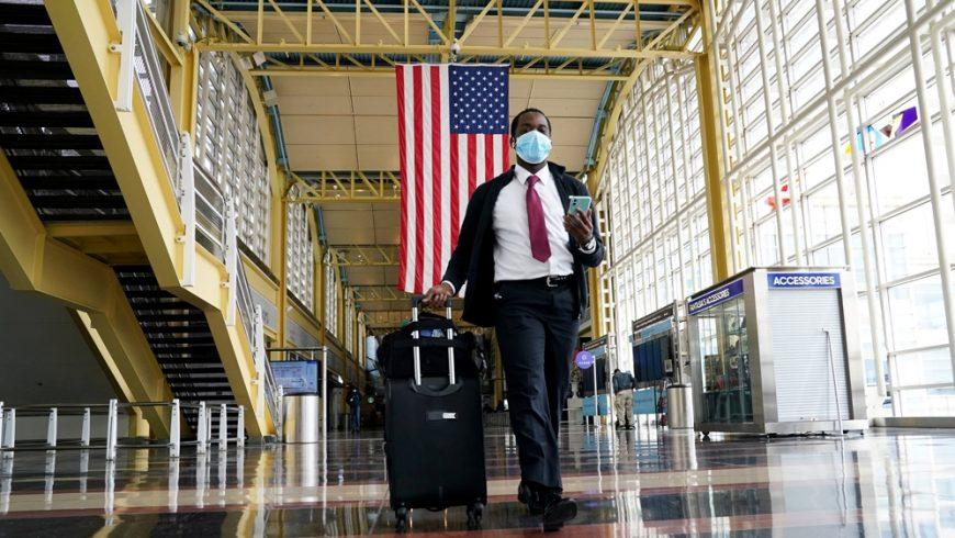 Seorang penumpang berjalan di Bandara Nasional Reagan di Washington, DC. Pihak Airlines menyatakan, penumpang bisa dilarang jika mereka menolak untuk memakai masker wajah. (Foto: Reuters/Al Jazeera)