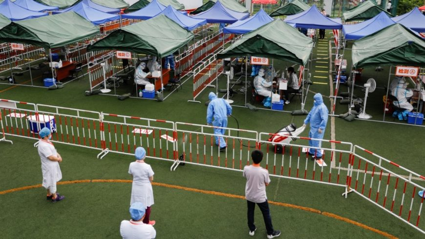 Seorang pekerja dalam pakaian pelindung menyemprotkan desinfektan ketika pekerja medis melakukan tes asam nukleat di sebuah lokasi pengujian di Beijing. (Foto Reuters/Al Jazeera)