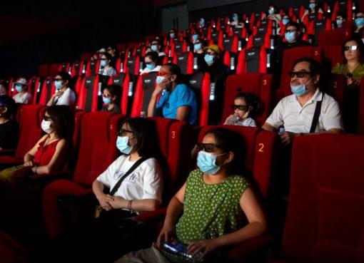 Dengan memakai masker wajah untuk melindungi diri dari virus corona, penonton di Beijing bisa menikmati film di bioskop. Ibukota China itu membuka kembali bioskop di beberapa bagian kota yang dianggap berisiko rendah.(Foto AP/Al Jazeera)