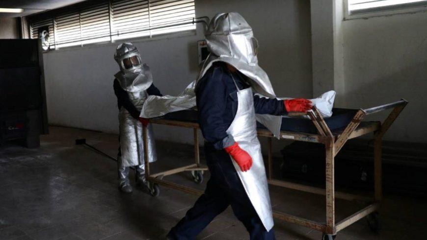 Para pekerja mengurusi kantung mayat yang berisi mayat seorang korban COVID-19 di sebuah krematorium di Mexico City pada hari Minggu. (Foto Reuters/Al Jazeera)